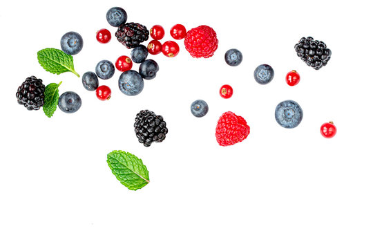Falling wild berries mix isolated on white background, top view. Strawberry, Raspberry, Blueberry and Mint leaf.
