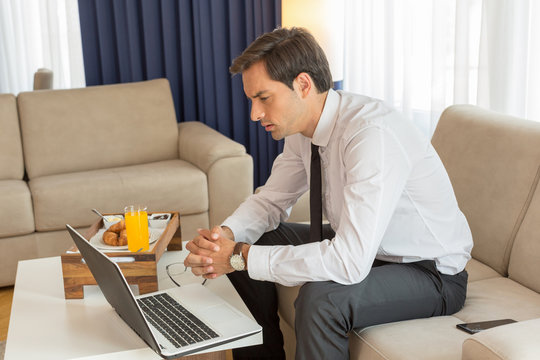 Handsome young businessman working on the notebook in a hotel room