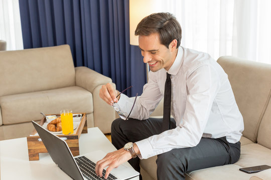 Happy handsome young businessman working on the notebook in a hotel room