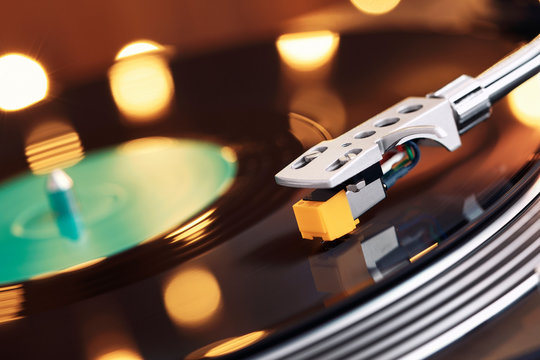 Turntable player with background of a stack of audition records and a Christmas tree. Sound technology DJ. Black vinyl record and stylus with needle. Christmas lights bokeh reflected on label surface