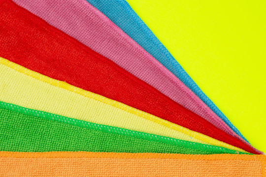 Set of colorful microfiber cleaning cloths on yellow background. Cleaning cloth for different purposes.
