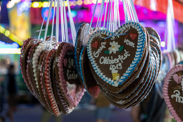 typical gingerbread hearts at the oktoberfest in munich 2019 at night with the words - gretting from the Oktoberfest