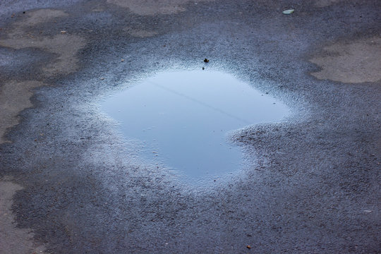 Drops of rain water on a fresh asphalt in the sun.