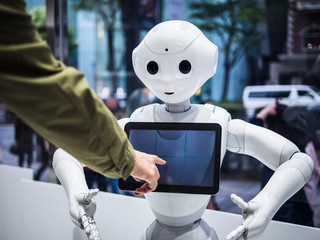 Pepper Robot Assistant Blank Information screen Japan Humanoid technology with people hand touch screen. TOKYO JAPAN - APR 16, 2018