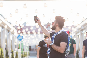 Handsome man is taking a selfie outdoor - caucasian people - nature, people, lifestyle and technology concept