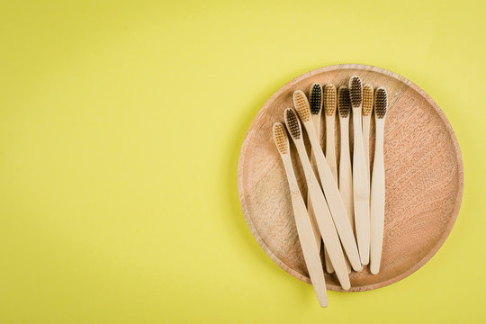 Flat lay composition with bamboo toothbrushes on wooden plate on grey background. Eco natural bamboo toothbrushes. Zero waste, plastic free items concept. Top view, copy space