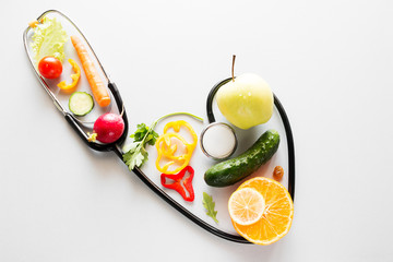 fruits and vegetables inside a stethoscope with heart shape diet vegetarian food concept