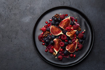 Fig, grape, raspberry and pomegranate salad on black plate