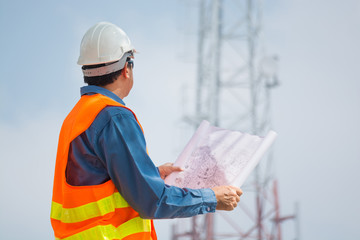 Engineer or Technocian hold plan and look at Telecommunication tower base