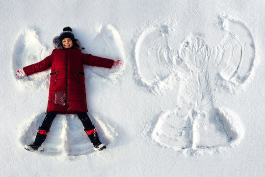 The girl lies in the snow and makes a snow angel