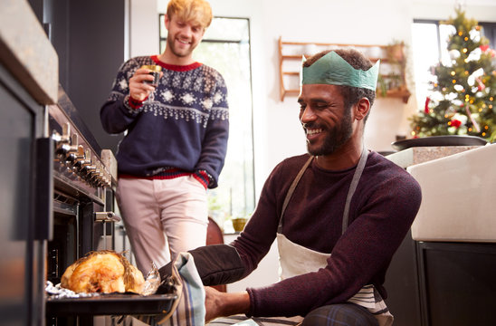 Gay Male Couple At Home In Kitchen Cooking Dinner On Christmas Day Together