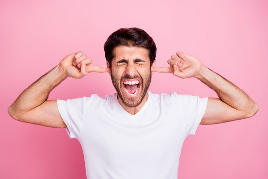 Stop irritating me. Portrait of upset negative emotions middle eastern man close cover ears index finger dont want listen argument with his wife wear trend clothes isolated pastel color background