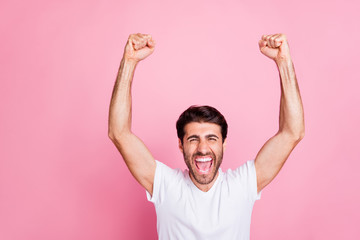 Portrait of ecstatic funny funky crazy lucky person middle eastern man raise fists scream yeah win competition have celebration wear white t-shirt isolated over pink color background