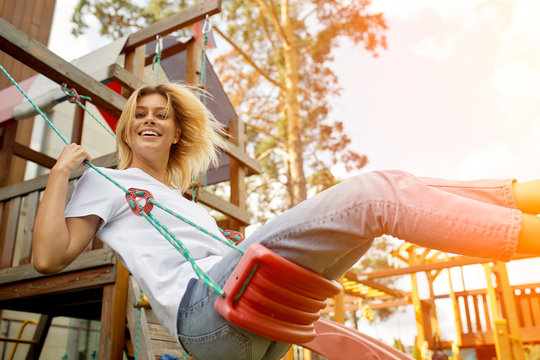 Carefree young woman playing on a rope swing leaning to the side laughing at the camera outdoors in a playground