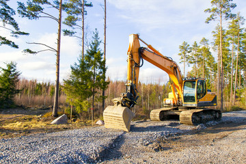 Yellow excavator building a road deep in the forest. Rusko, Finland.