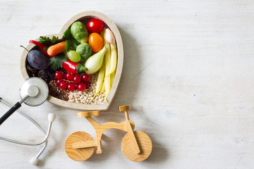 Healthy food in heart with stethoscope and bike diet sport lifestyle concept