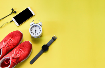Top view image with copy space of flat lay sport accessories on yellow background , sneakers ,smart warch, mobile phon with earphone ,vintage alarm clock. Running sport concept.