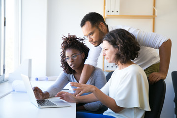 Instructor helping new employees with corporate software. Diverse man and women sitting and standing at desk, using computer, talking. Training concept