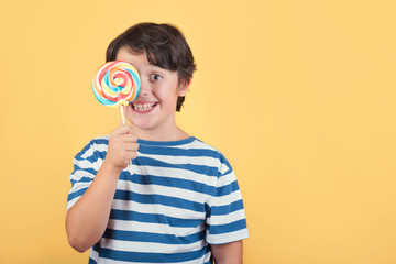 funny child covering eye with lollipop