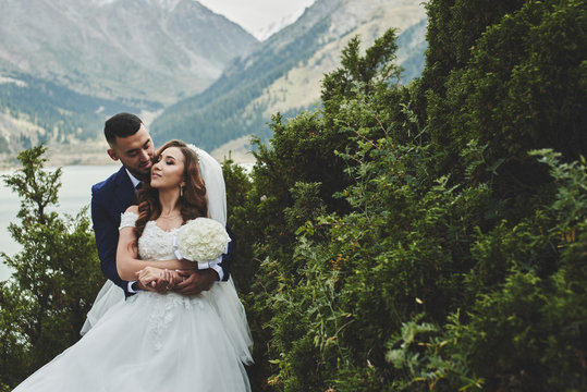 Beautiful wedding photo on mountain lake. Happy Asian couple in love, bride in white dress and groom in suit are photographed against background of the Kazakh landscape