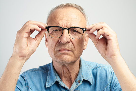 Old man in eye glasses with diopters squints, stares intently at the camera isolated on a white background. The concept of poor vision, senility blindness