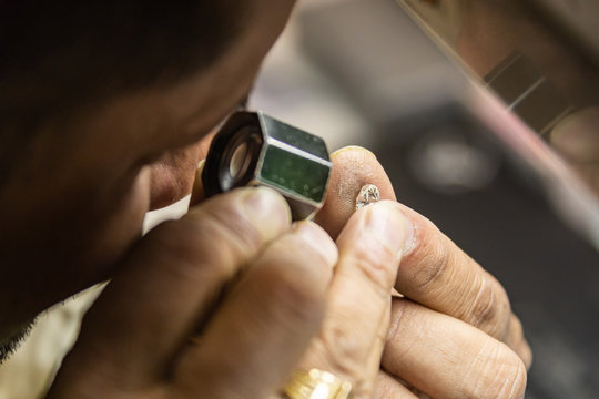 Botswana, african woman in a diamond factory checking quality of a newly polished diamond.