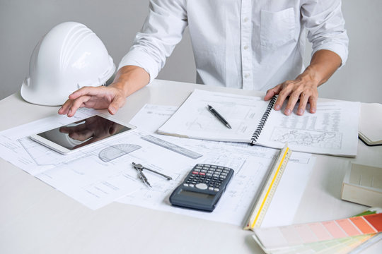 Architect working on blueprint, Engineer working with engineering tools for architectural project on workplace, Construction concept - building project, blueprints, ruler and dividers
