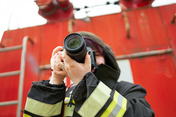 Image of young brunette fireman with photo camera in her hands on background of fire engines.