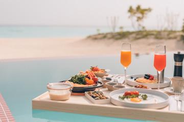 Breakfast in swimming pool, floating breakfast in tropical resort. Table relaxing in calm pool...