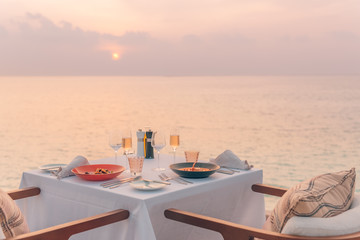 Romantic dinner on the beach. Wine glasses next to a beautiful dinner table setting, luxury resort hotel at beach view