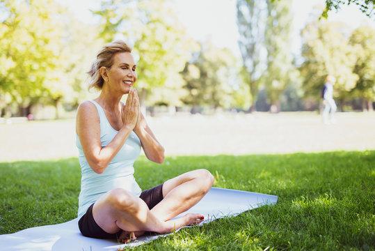 Frau im mittleren Alter meditiert im Park