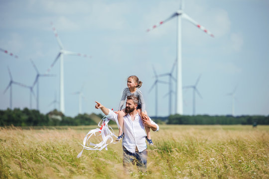 Mature father with small daughter walking on field on wind farm.