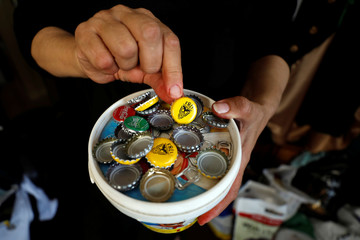 Palestinian woman Maha Shaltaf displays bottle caps that she collected to use them with other recycled items to create clothes and accessories, in Ramallah