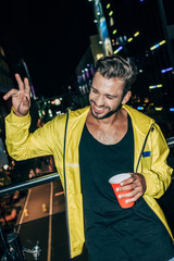 handsome man in yellow jacket showing peace sign and holding plastic cup in night city