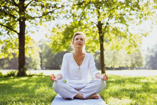 Eine attraktive Best-Ager Frau macht Meditations-Übungen im Park