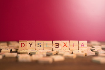 wooden alphabet blocks with DYSLEXIA word in the center on wooden table against pink background. Concept of Dyslexia awareness and human brain development