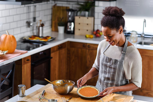 African american woman preparing pumpkin pie for holidays