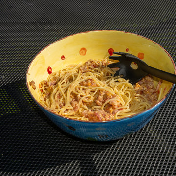 Bowl filled with spaghtetti carbonara on a table outdoors