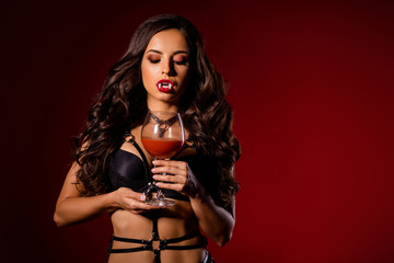 Portrait of nice attractive gorgeous evil black brunette wavy-haired lady vamp goth holding in hand drinking tomato blood juice concept isolated on dark red maroon burgundy marsala color background