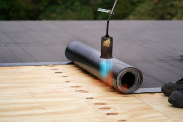 Bitumen roofing.,  with a gas burner and a roll of tar paper. Flat roof installation.