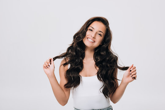 happy brunette beautiful woman with long curly healthy hair isolated on grey