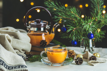 Christmas and New Year composition. Cup and teapot of hot spicy tea with sea buckthorn, jam in the glass jar, branches of pine and spruce, holiday decor, bokeh