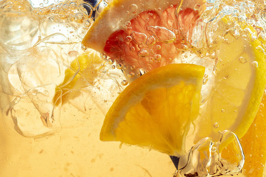 Close up of lemon slices in stirring the lemonade and ice cubes on background. Texture of cooling sweet summer's drink with macro bubbles on the glass wall. Fizzing or floating up to top of surface.