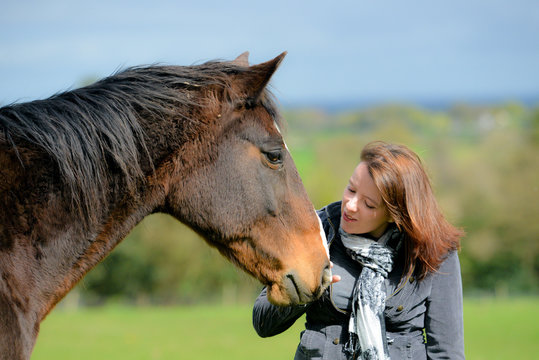 clsoe up shot of pretty young woman and her beautiful bay horse sharing a loving moment in the field.