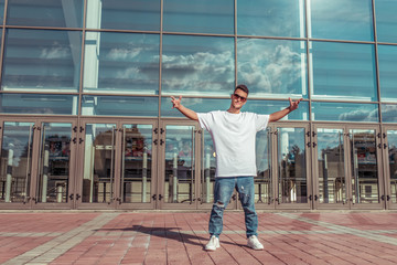 Man athlete, guy dancer in summer city. Glasses on background of glass windows. Fashionable modern break dance style, fitness sport hip hop. Urban culture, street dance. In t-shirt jeans sneakers.