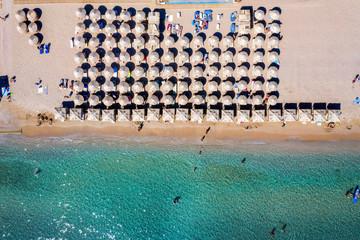 Wall Mural - Luftaufnahme eines Strandes mit Sonnenschirmen in der Reihe und Leute die im türkisem Wasser Spaß haben, bei Athen, Griechenland