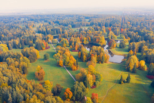 Aerial view flight over autumn valley park with meadows and a winding river, ponds, bright trees.