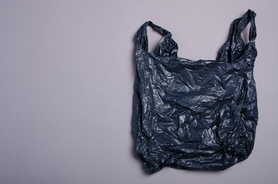 Clear disposable plastic bag on gray background. Space for text