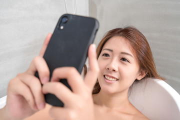Young and beautiful girl using phone relaxing in the retro bath indoors