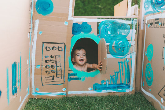 A happy baby in a painted cardboard box.